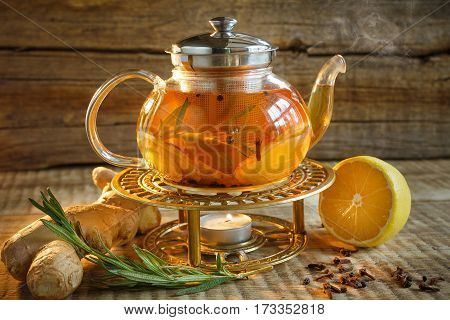 Glass tea pot with hot tasty tea with lemon, herbs,. Yellow lemon and tea. Tea pot on warm colors on wooden background. Herbal tea in a glass tea pot.