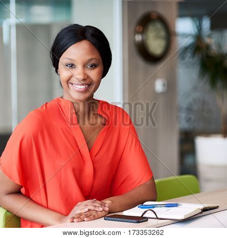 Square image of happy african woman smiling while looking into camera while wearimg a colourful orange blouse and sitting in a creative business lounge.