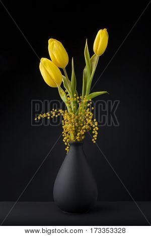 Bouquet of yellow tulips in black vase on black background