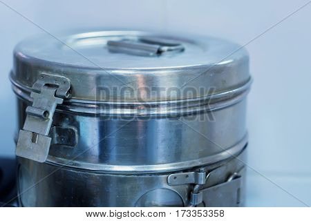 Medical crumpled and scratched round metal box for sterilization surgery tools in autoclave