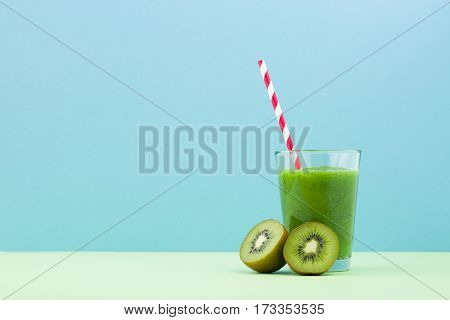 Fresh kiwi smoothie in the glass over blue background
