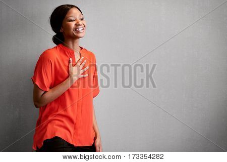Black female business person busy laughing with one hand against her chest while wearing a bright colourful orange blouse with space for copy text on the right of the image.