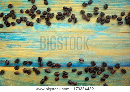 coffee beans on wooden background painted in blue and gold. place for text.