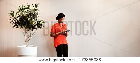 Black businesswoman holding a digital tablet in her hands while standing next to a tree planted in a pot against a textured wall with text space to the right of the image.
