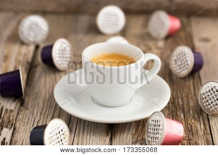 Fresh brewed espresso and used coffee capsules on wooden table. Natural light, selective focus.