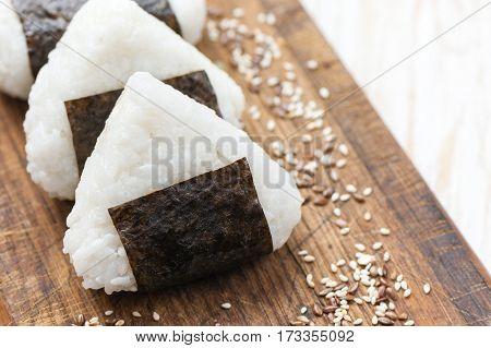 Onigiri. Rice triangle with nori seaweed on white plate.