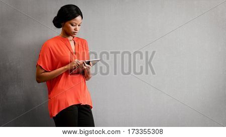 Young black businesswoman busy using the digital tablet that she is holding in her hands to conduct business remotely making use of the internet.