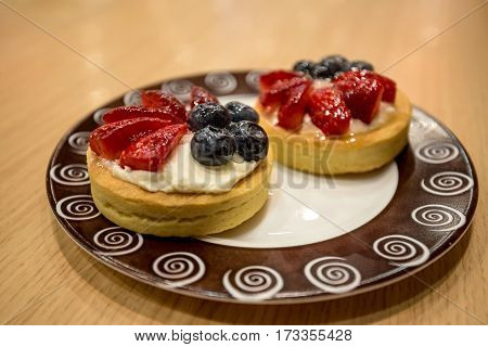 Beautiful tasty berry tartlet at cafe background