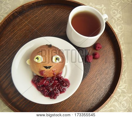Roll in the form of the boy, raspberry jam and tea. Creative food for children.