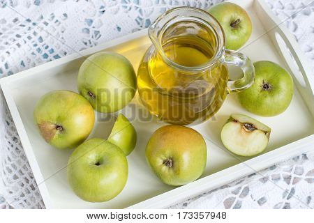 Source of natural vitamins. Small green apples and a glass jug with fresh apple juice on a white tray on openwork tablecloth.