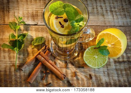 Ice tea with lemon splash. Hot yellow tea with lemon and many slices of lemon on wooden background, wooden table. Ginger tea with lemon on a wooden table. tea with lemon and mint.