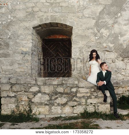 Stylish Luxury Bride And Groom Posing Together Near Old Castle Wall And Wooden Door At Sunset. Amazi