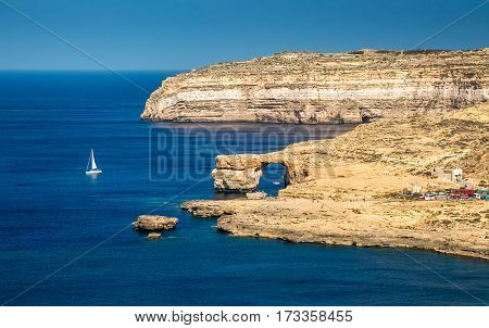 Gozo Malta - The Azure Window and Dwejra bay on a beautiful summer day with sail boat and clear blue sky