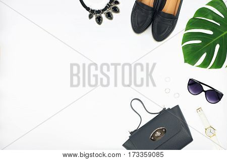 Overhead view of women's fashion set of accessories isolated on white background. Top view of denim jacket, leather bag, shoes, sunglasses and watch. Flat lay composition with space for copy