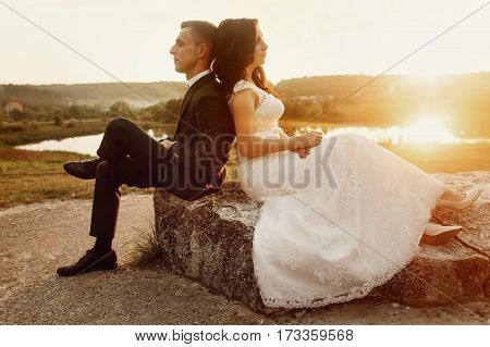 Romantic Couple Of Newlyweds Resting On Stone Bench At Sunset Field Near Lake Landscape, Happy Bride