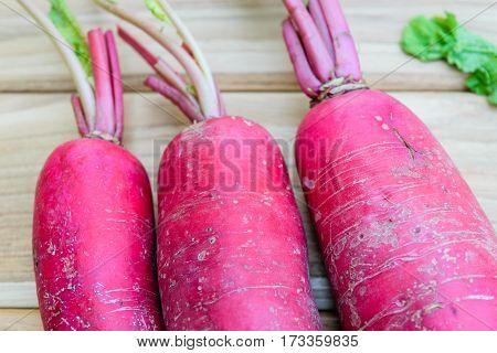 Three red radish on wooden table background