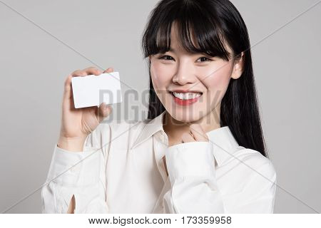 Studio portrait of twenties Asian woman enjoying having a card