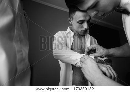 Handsome Groomsman Friends Helping Groom Put On Stylish White Shirt, Morning Wedding Preparation, Sm