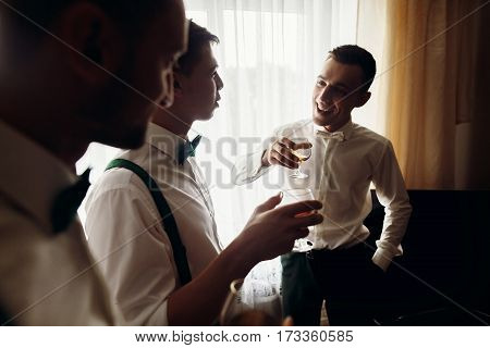 Handsome Groom And His Groomsman Friends In Stylish Suits Drink Whiskey In Hotel Room, Morning Befor