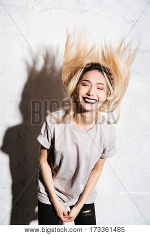 Cheerful young woman with black lips shaking her long blonde hair