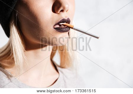 Closeup of attractive young woman smoking cigarette over white background