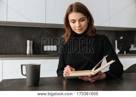 Photo of young pretty lady dressed in black sweater sitting at kitchen. Reading book.