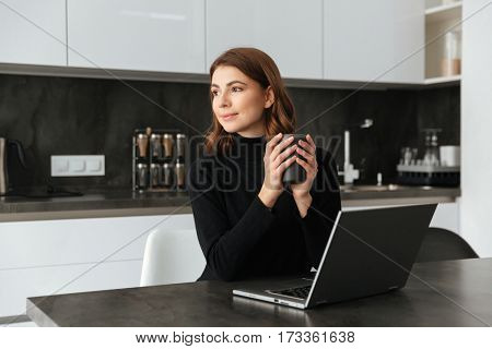 Picture of young incredible lady dressed in black sweater sitting at kitchen holding cup of coffee. Chatting by laptop.