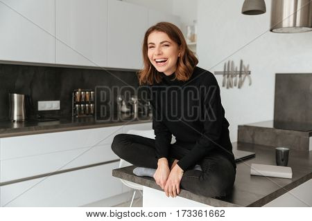 Photo of young happy woman dressed in black sweater sitting in kitchen at home indoors.