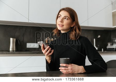Image of young amazing lady dressed in black sweater sitting at kitchen. Using mobile phone.