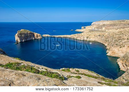 Gozo Malta - Panoramic skyline view of Dwejra bay with Fungus Rock Azure Window and sailboat on a nice hot summer day
