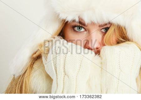 Winter clothing fashion concept. Closeup of young blue eyed woman covering her face with hands wearing white gloves. Attractive lady in wintertime clothes fur cap studio shot