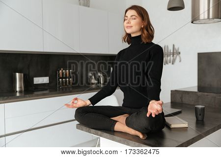 Image of young amazing woman dressed in black sweater sitting at home indoors. Make yoga exercises.