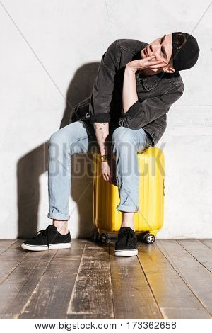 Vertical image of Hipster in snap back sitting and waiting on suitcase