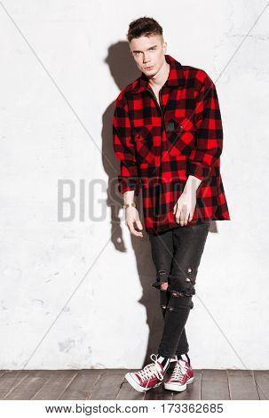 Vertical image of Hipster in shirt looking at camera. Full length portrait