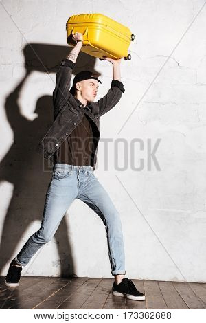 Vertical image of Hipster in snap back holding suitcase overhead. Side view