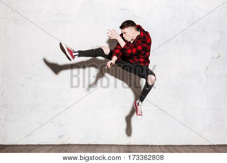 Hipster in red shirt jumping in studio. Full length portrait. Side view