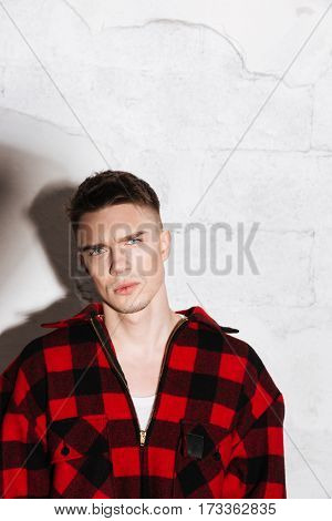 Vertical image of Serious Hipster in shirt posing in studio and looking at camera