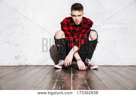 Hipster in shirt sitting near the wall and looking at camera