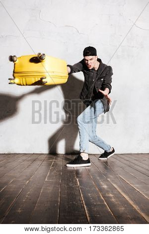 Vertical image of Hipster in snap back throwing suitcase at camera