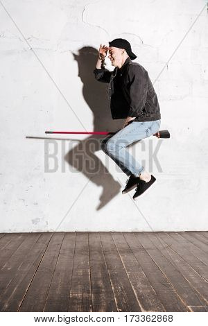 Vertical image of Hipster in snap back flying on mop. Side view