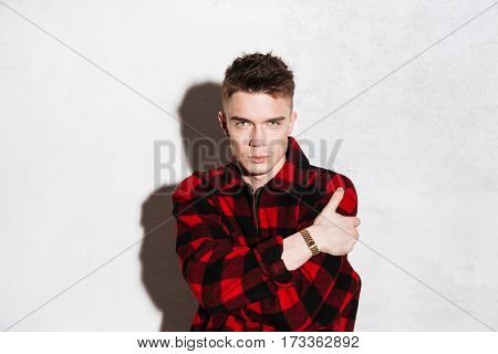 Hipster in shirt with crossed arms looking at camera