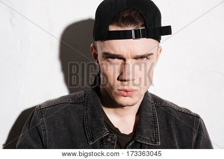 Close up portrait of serious hipster in snap back looking at camera over gray background