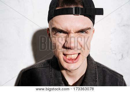 Close up portrait of Hipster in snap back grins and looks at camera over gray background