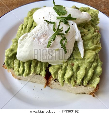 Healthy brunch poached eggs on a bed of smashed avocado with lime and chilli on focaccia bread toast on a white enamel plate