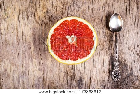 Half a grapefruit and a silver spoon on the old wooden background. A healthy breakfast. Fat loss and detox. Copy space.