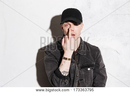 Hipster in snap back holding hand on face and showing middle finger over gray background