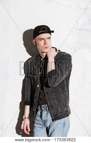 Vertical image of hipster in snap back and jeans shirt which looking away and posing near the gray wall