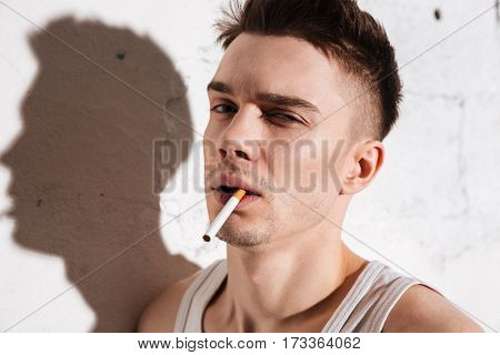 Portrait of young handsome man standing on floor with cigarette posing isolated over wall background. Looking at camera.