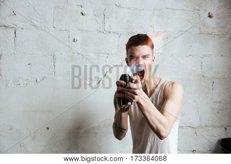 Photo of young man standing on floor with gas spray posing isolated over wall background. Looking aside and screaming.