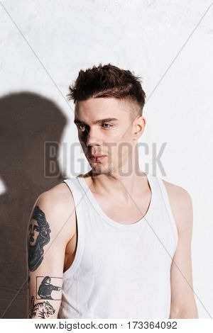 Portrait of handsome young man with tattoo on his hand over white background